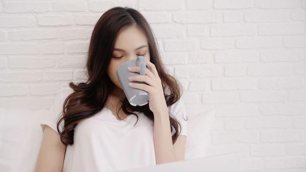 Piękna azjatycka kobieta bawić się komputer lub laptop podczas gdy kłamający na łóżku w jej sypialni.