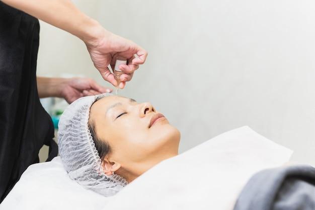 Piękna azjatycka kobieta coraz zabieg spa na twarz olejkiem z pipety na czystej skórze.