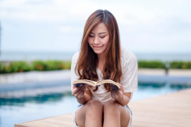 Piękna azjatycka kobieta czytająca książkę przy basenie z uczuciem relaksu?