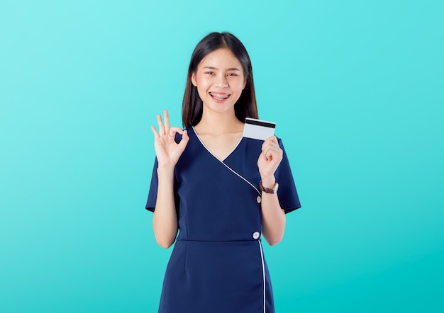 Piękna azjatycka kobieta dobra skóra, pokazuje ok znaka z być ubranym suknię i trzymać płatność kartą kredytową na błękitnym tle.