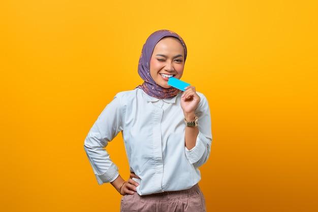 Piękna azjatycka kobieta gryząca pustą kartę i patrząca na kamerę na żółtym tle