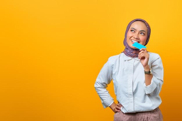 Piękna azjatycka kobieta gryząca pustą kartę i patrząca w górę z uśmiechniętą twarzą na żółtym tle