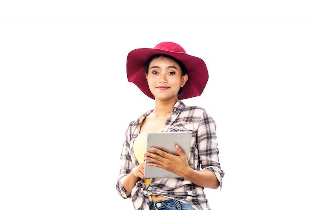 Piękna azjatycka kobieta jest ubranym czerwonego kapelusz, stoi z pastylką, ścinek ścieżka