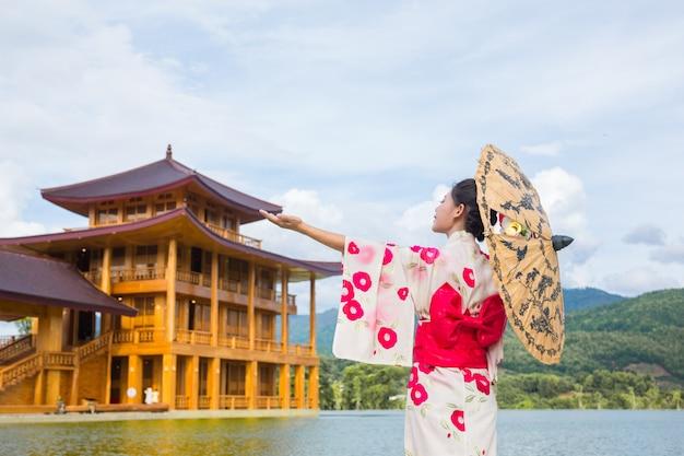 Piękna azjatycka kobieta jest ubranym japońskiego kimono, tradycyjny smokingowy pojęcie.