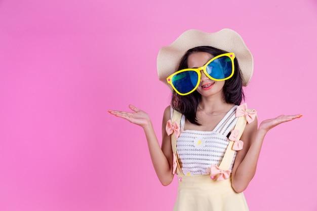 Piękna azjatycka kobieta jest ubranym kapelusz i duże szkła z menchiami.
