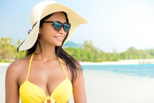 Piękna azjatycka kobieta jest ubranym żółtego bikini swimsuit przy plażą w lecie