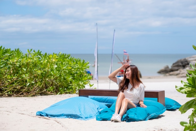 Piękna azjatycka kobieta lubi siedzieć i relaksować się na krześle z fasoli na plaży