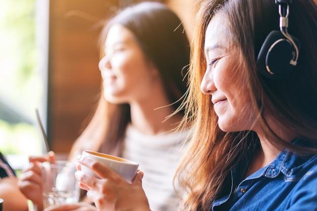 Piękna azjatycka kobieta lubi słuchać muzyki przez słuchawki podczas picia kawy z przyjaciółmi