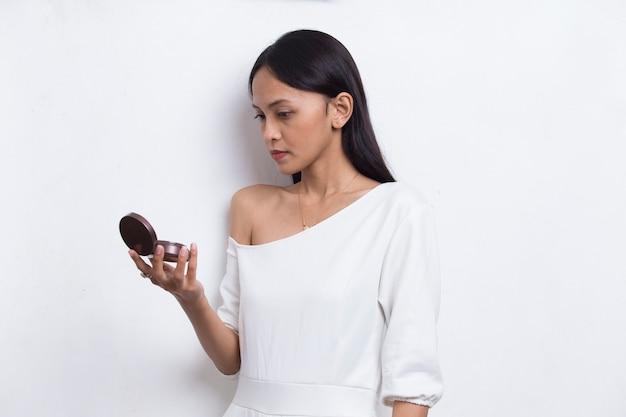 Piękna azjatycka kobieta nakłada proszek na makijaż kosmetyku na białym tle
