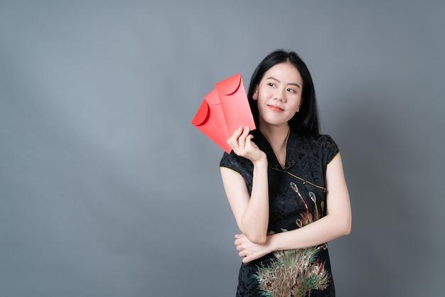 Piękna azjatycka kobieta nosi chińską tradycyjną sukienkę z czerwoną kopertą lub czerwoną paczką