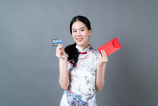 Piękna azjatycka kobieta nosi chiński tradycyjny strój z czerwoną kopertą lub czerwoną paczką i kartą kredytową na szarej ścianie