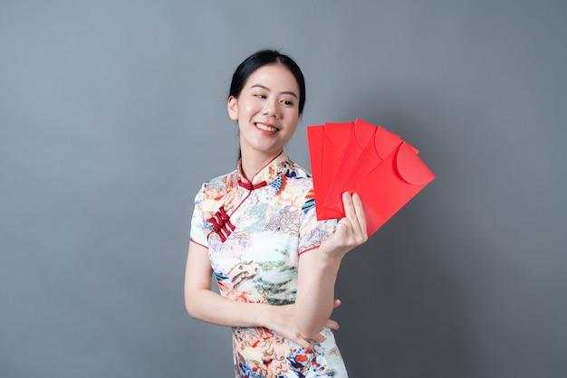 Piękna azjatycka kobieta nosi chiński tradycyjny strój z czerwoną kopertą lub czerwoną paczką na szarej ścianie