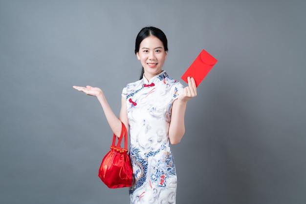 Piękna azjatycka kobieta nosi chiński tradycyjny strój z czerwoną kopertą na szarej powierzchni