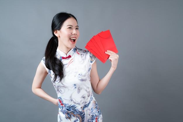 Piękna azjatycka kobieta nosi chiński tradycyjny strój z czerwonymi kopertami na szarej powierzchni