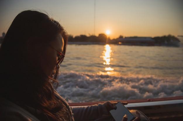 Piękna azjatycka kobieta ogląda hermobile w łodzi.