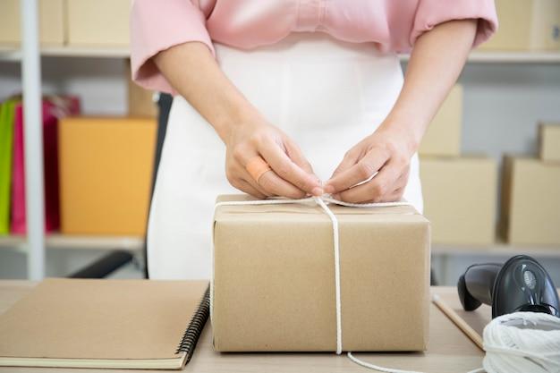 Piękna azjatycka kobieta pakuje paczkę pocztową na stole, zakupy online i e-commerce w małej firmie rozpoczynającej działalność.