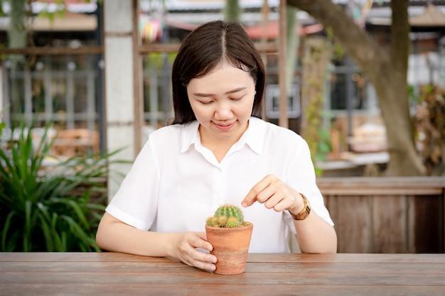 Piękna azjatycka kobieta patrzeje małego kaktusa w cray garnku