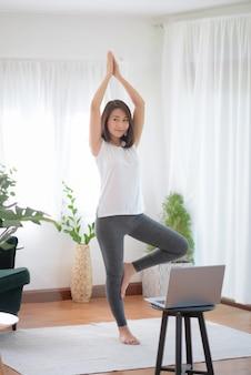 Piękna azjatycka kobieta pozostaje sprawna, ćwicząc w domu dla zdrowego stylu życia