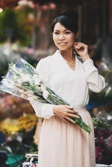 Piękna azjatycka kobieta pozuje z wielkim bukietem w kwiatu sklepie