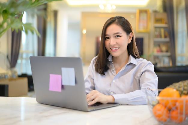 Piękna azjatycka kobieta pracuje na swoim komputerze w domu.
