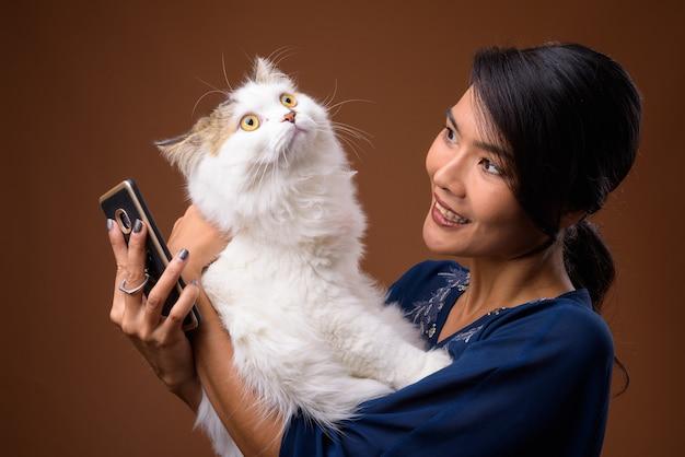 Piękna azjatycka kobieta przed brązową ścianą