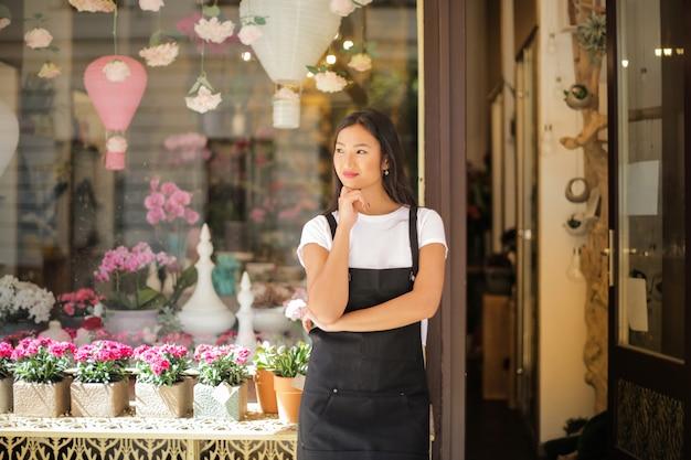 Piękna azjatycka kobieta przed jej sklepem