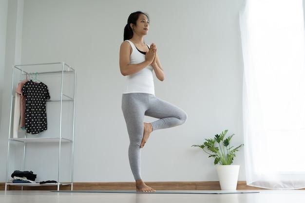 Piękna azjatycka kobieta robi joga w domu. kobiety utrzymują równowagę w pozycji drzewa i ćwiczą powolny wdech i wydech. koncepcja zdrowia i fitness