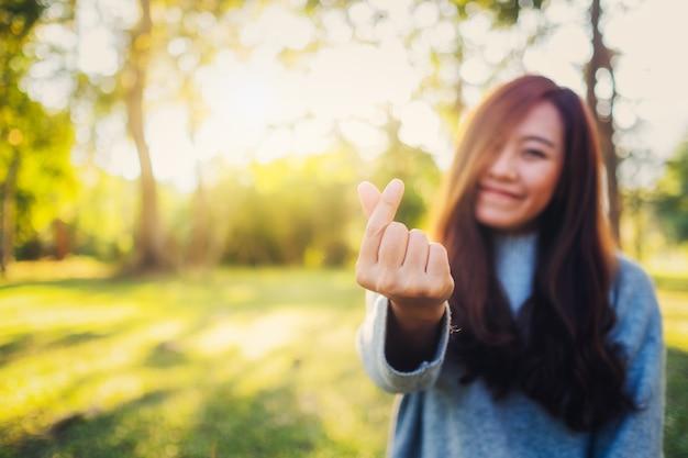 Piękna azjatycka kobieta robi mini-serce znak ręką w parku przed zachodem słońca