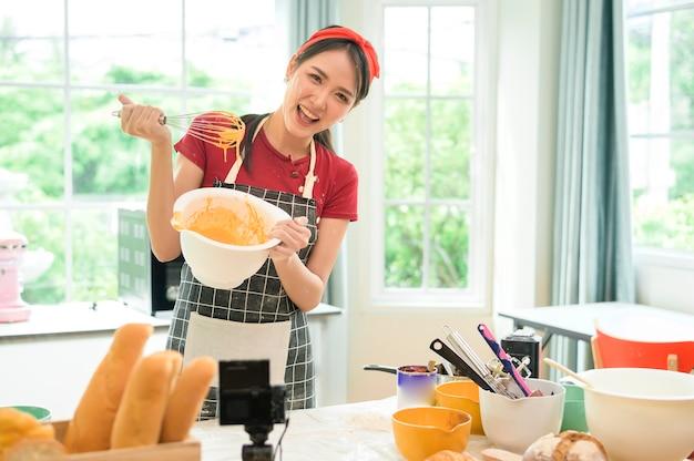 Piękna azjatycka kobieta robi piekarnię, transmituje na żywo lub nagrywa wideo w mediach społecznościowych w swoim domu