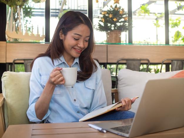 Piękna azjatycka kobieta siedzi czytając książkę na kanapie. trzymając kawę i uśmiechając się zrelaksowany