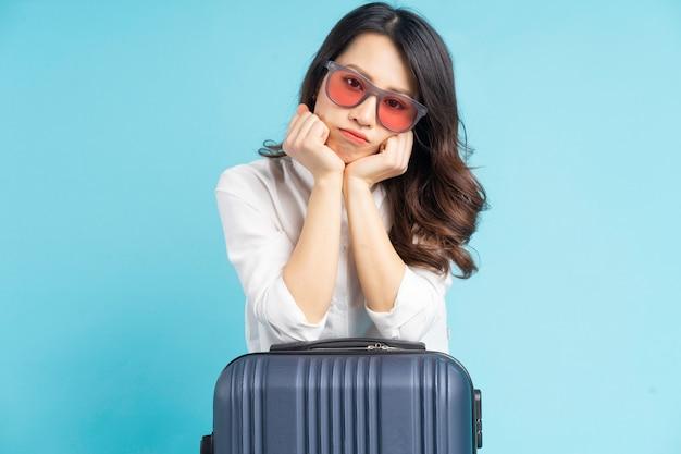 Piękna azjatycka kobieta siedzi obok walizki i przygotowuje się do podróży