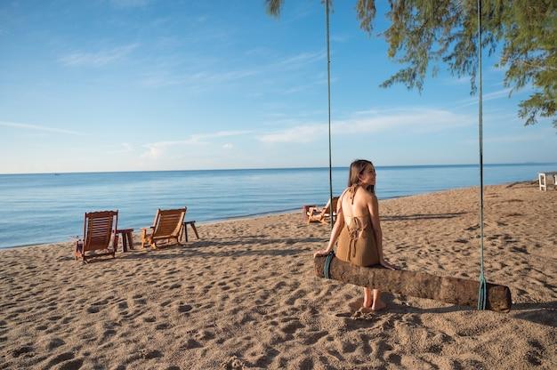 Piękna azjatycka kobieta siedzi przy drewnianej huśtawce na plaży w tropikalnym morzu o poranku