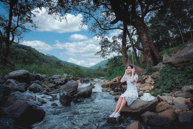 Piękna azjatycka kobieta, słuchanie muzyki nad rzeką