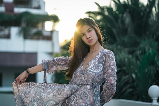 Piękna azjatycka kobieta tańczy ze spódnicą z zachodem słońca lekką silhoutte bedhind dla wolności i relaksującej koncepcji.