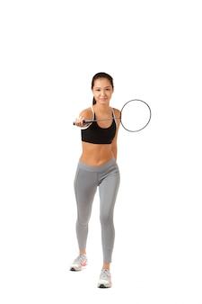Piękna azjatycka kobieta trzyma badminton kant odizolowywający na białym tle