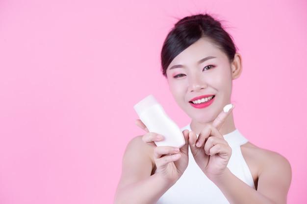Piękna azjatycka kobieta trzyma butelkę produkt na różowym tle.