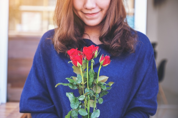 Piękna azjatycka kobieta trzyma czerwone róże kwiat z uczuciem szczęścia na walentynki