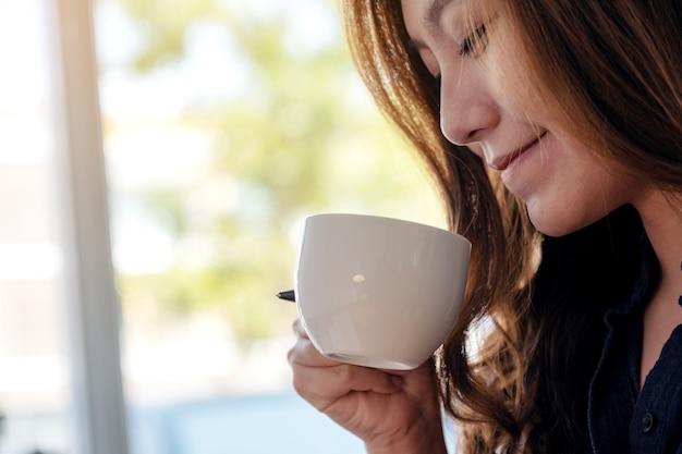 Piękna azjatycka kobieta trzyma i pije gorącą kawę z dobrym samopoczuciem w kawiarni