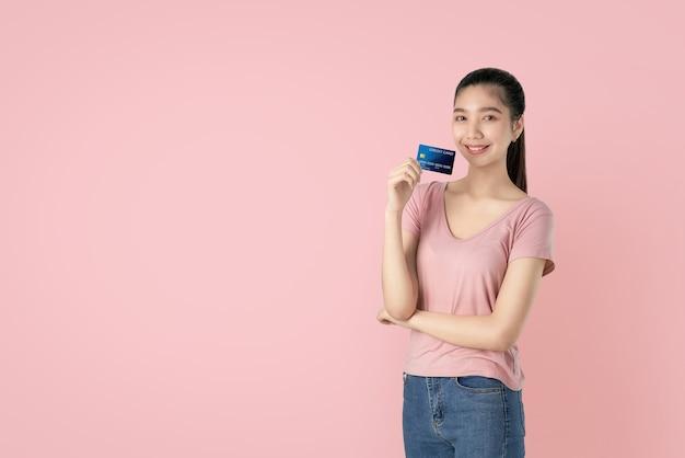 Piękna azjatycka kobieta trzyma kredytowej karty zapłatę na różowym tle z kopii przestrzenią.