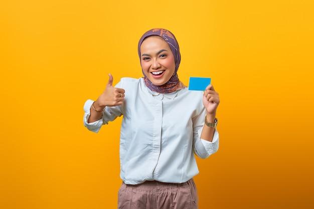 Piękna azjatycka kobieta trzyma pustą kartę i pokazuje kciuki z uśmiechniętą twarzą