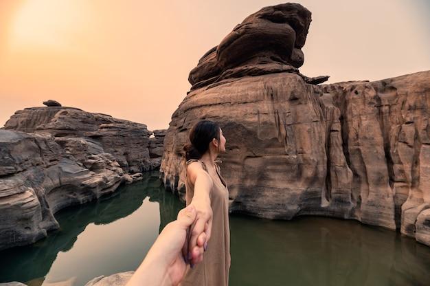 Piękna azjatycka kobieta trzymając się za ręce z parą w skalnym wąwozie wielkiego kanionu wieczorem