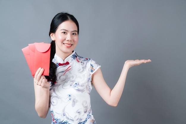 Piękna azjatycka kobieta ubrana w chińską tradycyjną sukienkę z czerwoną kopertą lub czerwoną paczką na szaro