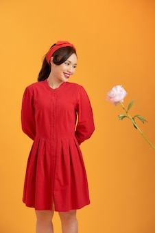 Piękna azjatycka kobieta ubrana w czerwoną sukienkę i stojąca na pomarańczowym tle