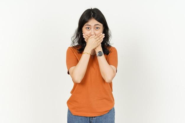 Piękna azjatycka kobieta ubrana w pomarańczową koszulkę w szoku i zakrywającą usta