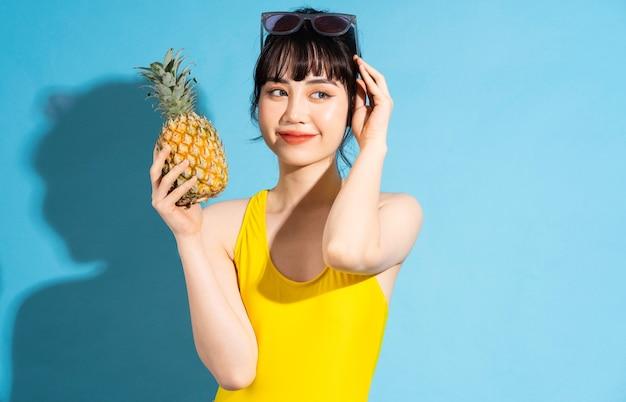 Piękna azjatycka kobieta ubrana w żółty kombinezon na niebiesko i je owoce tropikalne