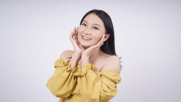 Piękna azjatycka kobieta uśmiecha się pokazując swój makijaż na białym tlepiękna azjatycka kobieta uśmiecha się pokazując swój makijaż na białym tle