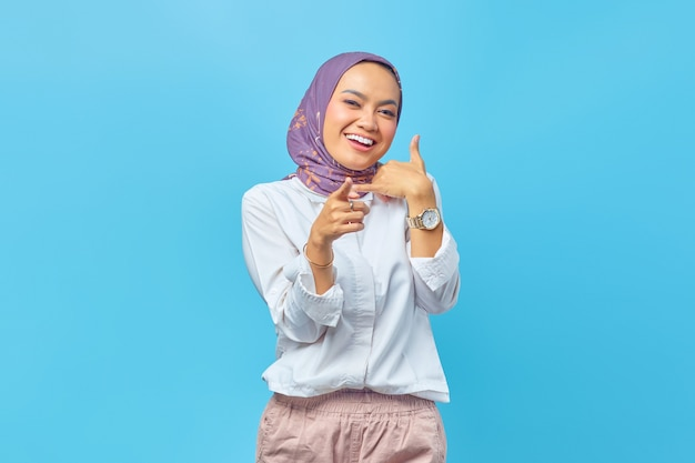 Piękna azjatycka kobieta uśmiecha się wykonując gest połączenia ręką, wskazując palcem wskazującym na aparacie