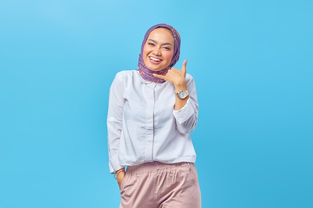 Piękna azjatycka kobieta uśmiecha się wykonując gest połączenia ręką