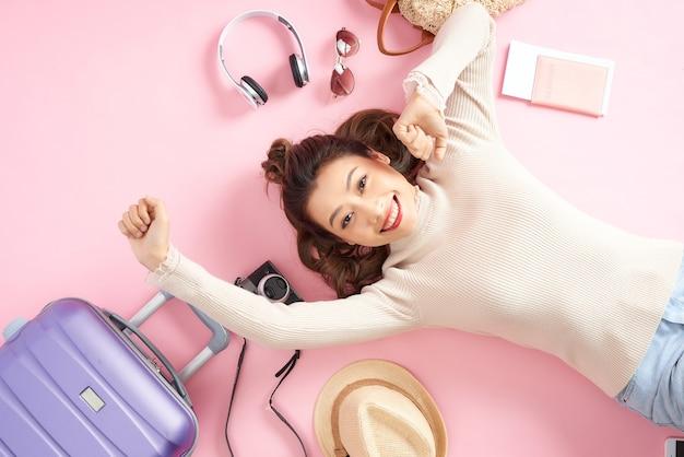 Piękna azjatycka kobieta uśmiechnięta szczęśliwie i leżąca na różowej podłodze