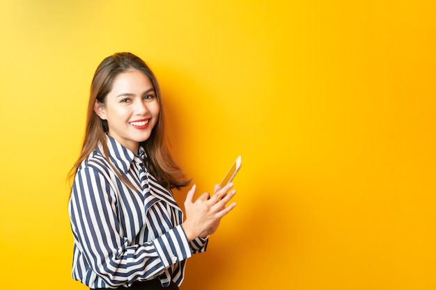 Piękna azjatycka kobieta używa jej pastylkę na żółtym tle